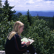 Young girl painting a picture from her perch on a mountaintop