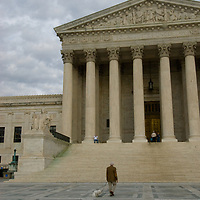 A man walks his dog in front of the U.S. Supreme Court building in Washington, DC.
