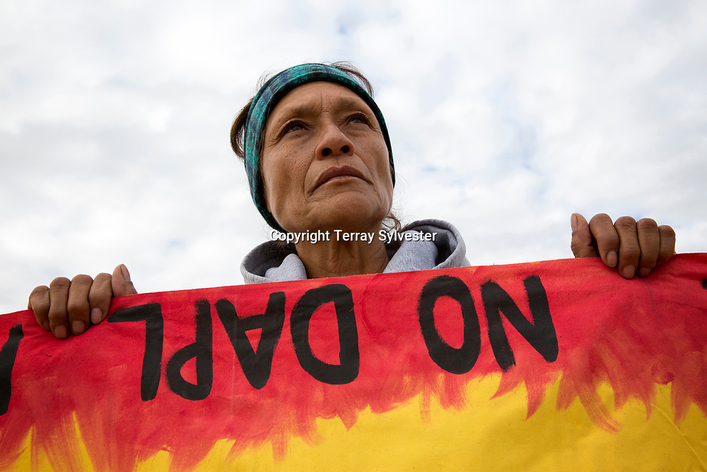 Dolores Moreno of the Juañeno Band of Mission Indians in California holds a banner during a rally against the Dakota Access oil pipeline on the state capitol grounds in Bismarck, ND, on November 14, 2016.