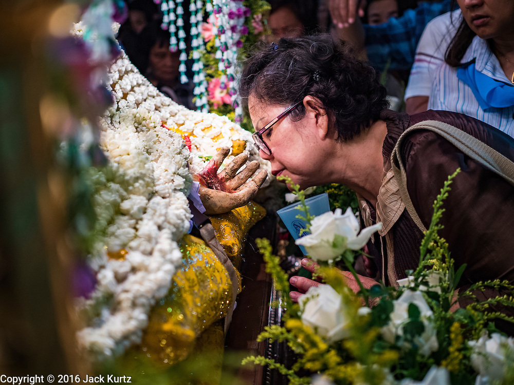 25 MARCH 2016 - BANGKOK, THAILAND:  People kiss the hand of a statue of Jesus during Good Friday observances at Santa Cruz Church in Bangkok. Santa Cruz was one of the first Catholic churches established in Bangkok. It was built in the late 1700s by Portuguese soldiers allied with King Taksin the Great in his battles against the Burmese who invaded Thailand (then Siam). There are about 300,000 Catholics in Thailand, in 10 dioceses with 436 parishes. Good Friday marks the day Jesus Christ was crucified by the Romans and is one of the most important days in Catholicism and Christianity.     PHOTO BY JACK KURTZ