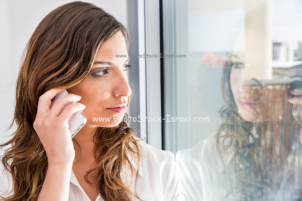 failed young business woman reflects in her office window as she talks on a mobile phone