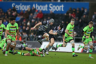 Ben John of the Ospreys © steps over a tackle from Nic Groom of Northampton (on ground) as he makes a break with Dan Lydiate of the Ospreys jumping in support. European Rugby Champions Cup, pool 2 match, Ospreys v Northampton Saints at the Liberty Stadium in Swansea, South Wales on Sunday 17th December 2017.<br /> pic by  Andrew Orchard, Andrew Orchard sports photography.