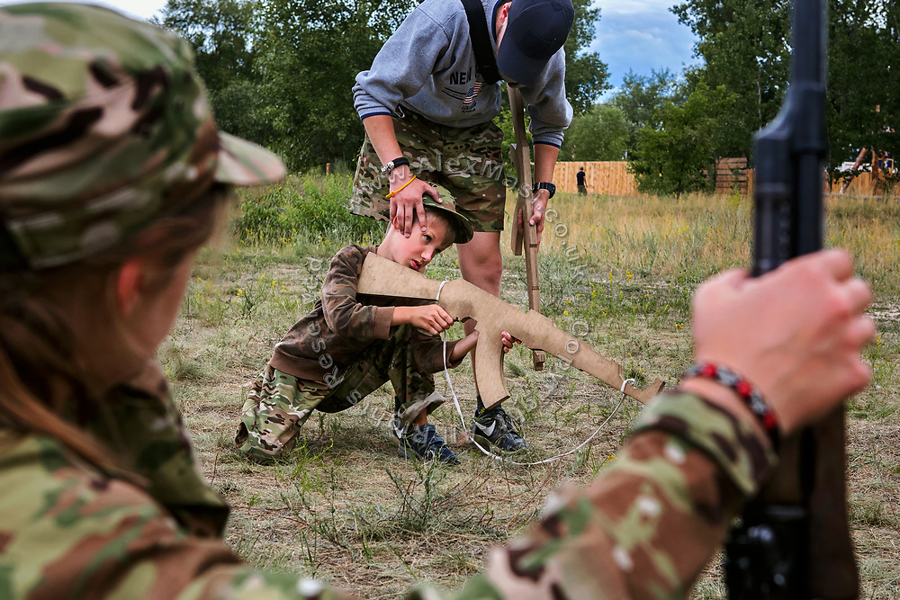 A young boy participating to the ultra-nationalistic Azovets children's camp is being held by his instructor into the correct position to point a wooden rifle, during tactical training on the banks of the Dnieper river, in Kiev, Ukraine's capital.
