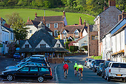 Cyclists on touring holiday cycling past parked cars through the old town of Dunster, in Somerset, UK