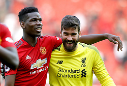Manchester United's Paul Pogba (left) and Liverpool goalkeeper Alisson Becker share a laugh at the end of the Premier League match at Old Trafford, Manchester.