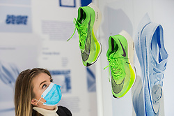 "© Licensed to London News Pictures. 20/10/2020. LONDON, UK. A staff member views the ""Nike Zoom X Vaporfly NEXT%"" running shoes by designers at Nike Sport Research, as worn by Eliud Kipchoge to break the two hour marathon barrier.  Preview of the Beazley Designs of the Year at the Design Museum in Kensington.  The most innovative designs from January 2019 to the moment the COVID-19 pandemic took hold are on display 21 October to 28 March 2021.  Photo credit: Stephen Chung/LNP"