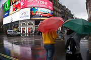 London, UK. Sunday 23rd August 2015. Heavy summer rain showers in the West End. People brave the wet weather armed with umbrellas and waterproof clothing. Piccadilly Circus.