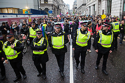 London, UK. 14 October, 2019. City of London Police officers walk ahead of climate activists from Extinction Rebellion after they decided to vacate the busy junction in front of the Bank of England which they had occupied since 7am on the eighth day of International Rebellion protests.