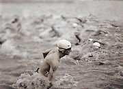 A man rises out of the water while competing in a triathalon