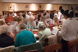 Elderly people eating meals in function room,