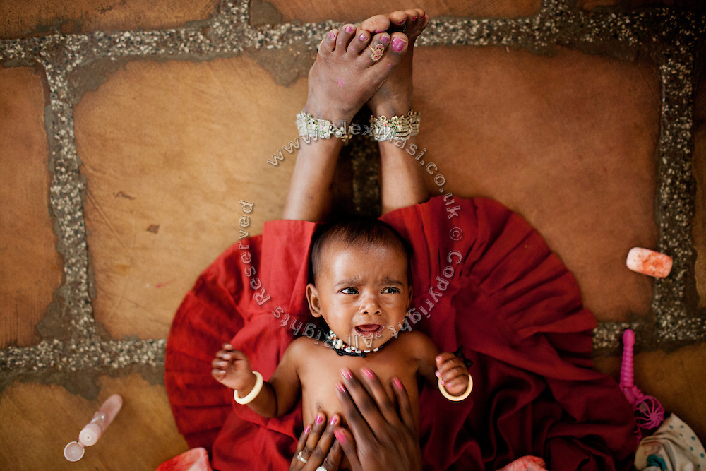 A mother is cleaning and oiling her malnourished child while sitting on the floor of a feeding centre run by UNICEF in the town Shivpuri, Madhya Pradesh, India.