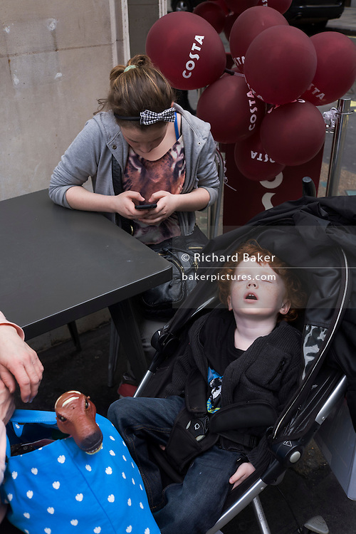 A sleeping auburn-haired boy sleeps soundly in his buggy during a daytrip to London.