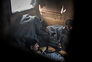 Migrants are seen through a door window inside an abandoned train wagon where they have found shelter.  Belgrade, Serbia. January 16th 2017. Federico Scoppa