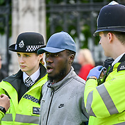A young black man shouting at the Parliament building. Why you takes my passport. He get more angry defending himself, Why you arrest me? Police arrest him outside Parliament square, London, UK. 2019-09-15.