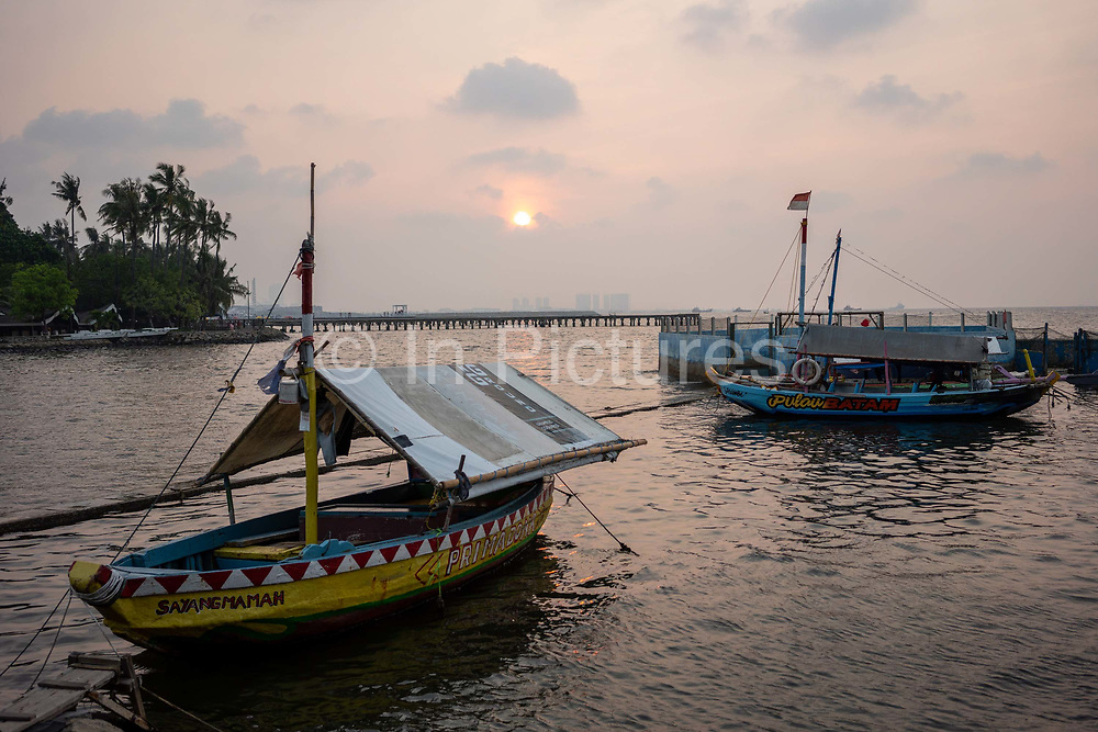 Boats sit at the harbour as the sun goes down on 9th June 2018 in Jakarta, Java, Indonesia.