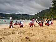 26 DECEMBER 2014 - PATONG, PHUKET, THAILAND: Thai high school students dig holes for candles for the candle light memorial to mark the anniversary of the tsunami on Patong Beach in Patong, Phuket. Hundreds of people died in Patong and nearly 5400 people died on Thailand's Andaman during the 2004 Indian Ocean Tsunami that was spawned by an undersea earthquake off the Indonesian coast on Dec 26, 2004. In Thailand, many of the dead were tourists from Europe. More than 250,000 people were killed throughout the region, from Thailand to Kenya. There are memorial services across the Thai Andaman coast this weekend.    PHOTO BY JACK KURTZ