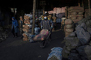 A coal merchant carries a sack of coal for a customer in Kabul, Afghanistan, February 2, 2020. The capital Kabul, a city of some 6 million, ranks as one of the most polluted cities in the world – contesting amongst other polluted capitals such as India's New Delhi or China's Beijing. Many cannot afford electricity and so burn coal, garbage, plastic and rubber in their homes to keep warm during the cold winter months. Old vehicles and generators that run on poor quality fuel release vast amounts of toxins into the city's air.
