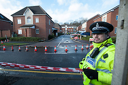 © London News Pictures. 15/02/2014. Hemel Hempstead, UK.  A policeman walking in front of a property which has been cordoned off after a giant sinkhole measuring 35ft wide by 20ft deep has opened up next to a house in Hemel Hempstead, Hertfordshire.  Photo credit: Ben Cawthra/LNP