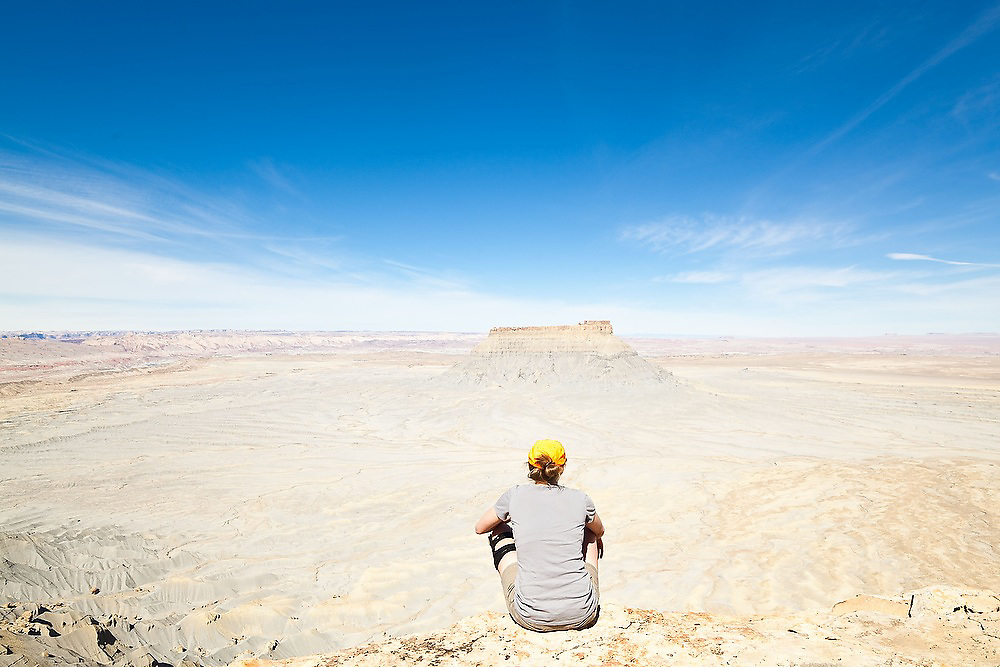 A young woman looks out from the rim of North Caineville Mesa towards Factory Butte, Utah.