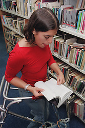 Teenage girl with physical disability looking through book in college library,