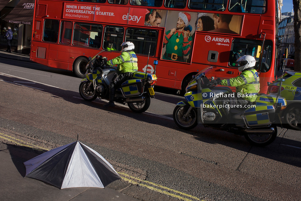A discarded broken umbrella and police motorcyclists in traffic in Charing Cross Road, central London.