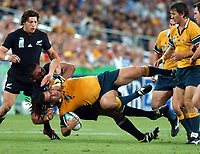 Photo. Steve Holland.Australia v New Zealand, Semi-final at the Telstra Stadium, Sydney. RWC 2003.<br />15/11/2003.<br />George Smith is tackled by  Jerry Collins