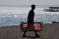 © Licensed to London News Pictures. 18/07/2013<br /> As the heatwave continues across the UK today (18.07.2013)<br /> People enjoy the  heatwave  in Hastings,East Sussex.<br /> Young man collecting the deck chairs at the end of the day.<br />  Photo credit :Grant Falvey/LNP