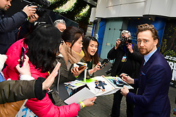 Tom Hiddleston signs autographs for fans during the Early Man World Premiere held at the BFI Imax, London.