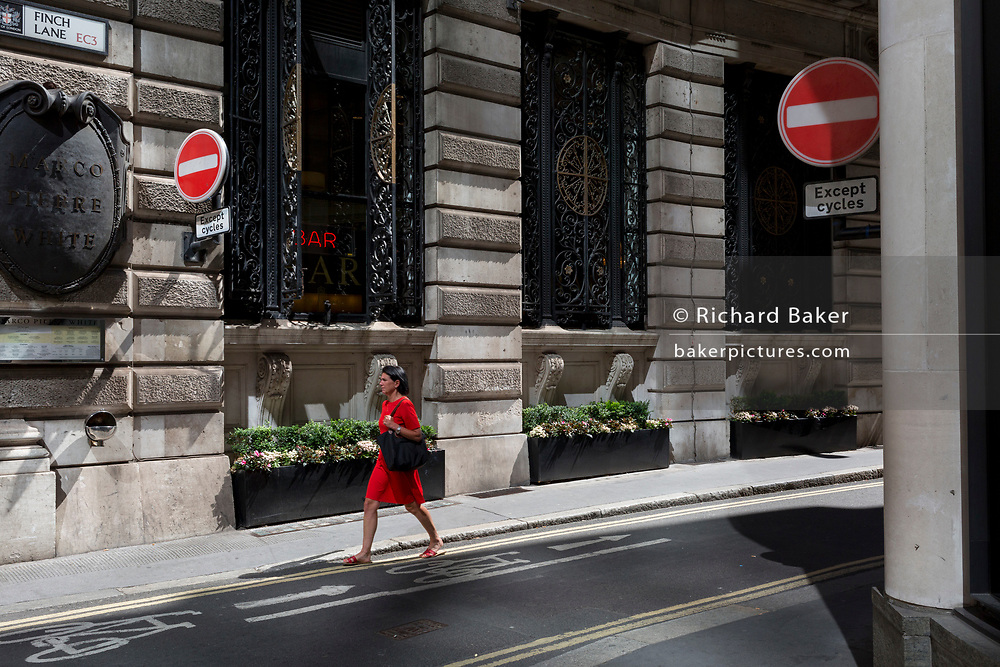 A lady in a red dress walks on Finch Street, a narrow medieval-era lane in the City of London, the capital's historic financial district, on 2nd August 2018, in London, England.