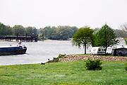Nederland, Slijk Ewijk, 23-4-2019Een binnenvaartschip vaart over de Waal richting Rotterdam . Het passeert juist  de camping de Grote Altena die aan de Waal ligt . Foto: Flip Franssen
