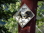 """""""Tourists Crossing"""" sign shows a bear delightfully chasing a person with camera. Cottonwood RV Park, Kluane Lake, Yukon, Canada."""