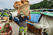 "10 JUNE 2014 - YANGON, MYANMAR:   A porter unloads coconuts from a riverboat on the banana jetty. The ""banana jetty"" is on the Yangon River north of central Yangon on Strand Road. Bananas, coconuts and other fruit are brought in here from upcountry, sold and reshipped to other parts of Myanmar (Burma). All of the labor here is done by hand. Porters carry the produce to the jetty and porters load the boats before they steam upriver.   PHOTO BY JACK KURTZ"