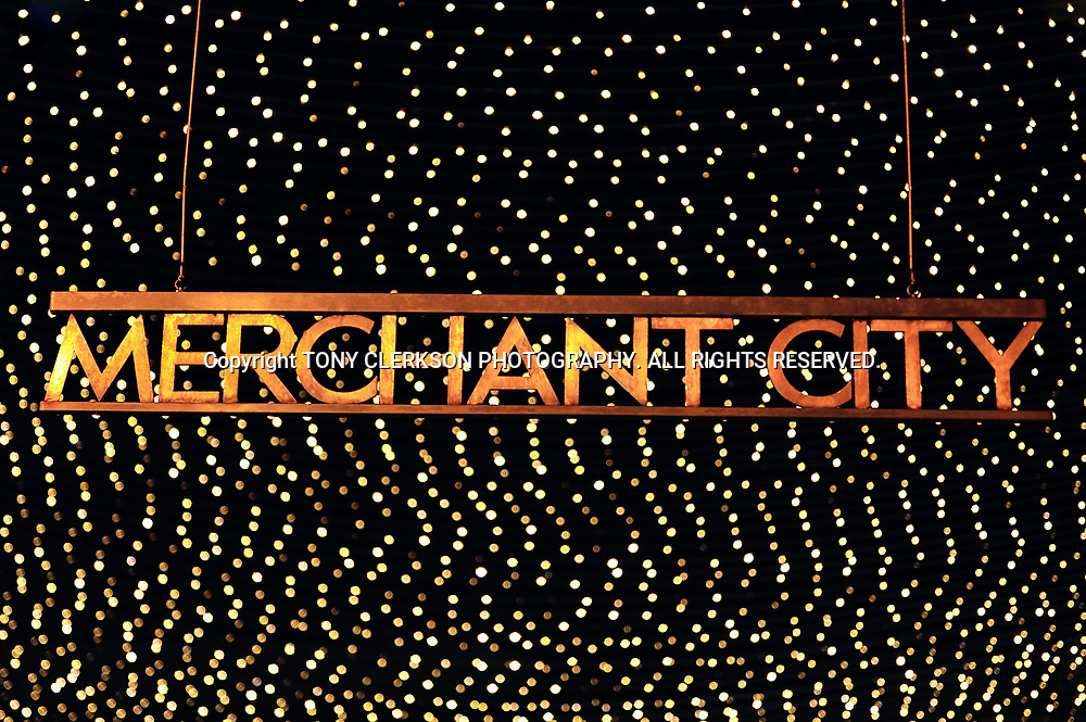 The Merchant City sign in Royal Exchange Square, Glasgow city centre, lit up at night against a twinkling backdrop.