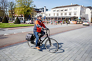 In Zeist rijdt een oudere man op een e-bike door het centrum.<br /> <br /> Cyclists in the city center of Zeist.