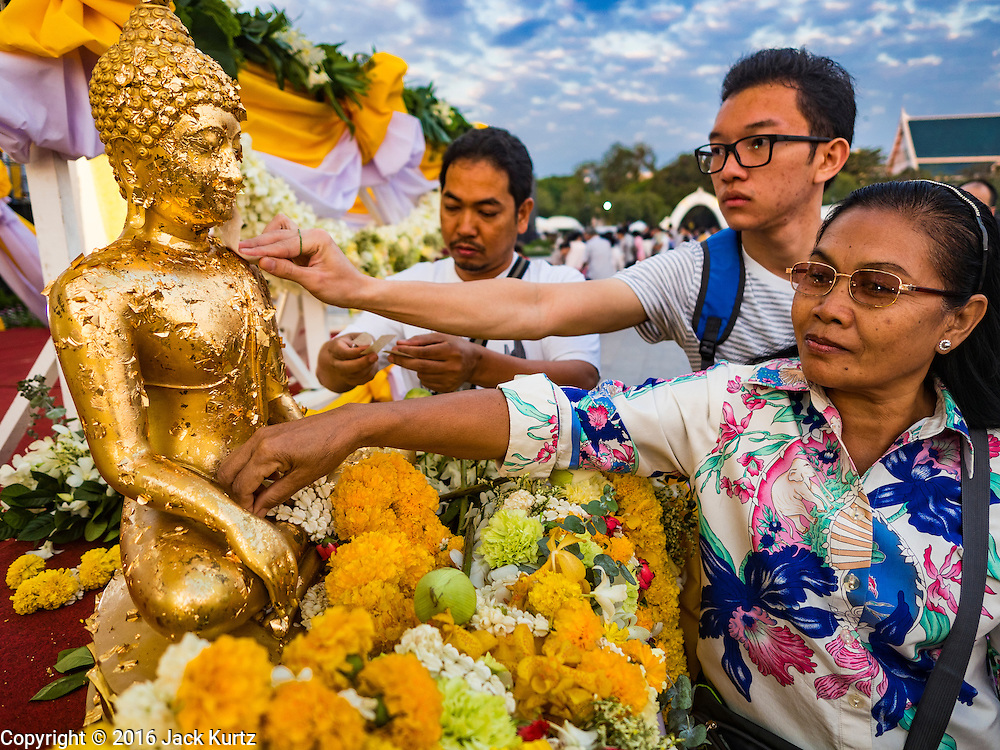 01 JANUARY 2016 - BANGKOK, THAILAND:          People apply gold leaf to a statue of the Buddha during the annual New Year's mass merit making ceremony on at Sanam Luang in Bangkok. The ceremony is sponsored by the Bangkok city government. More than 500 Buddhist monks participated in the ceremony this year. Thais usually go to temples and religious observances to meditate and make merit on New Year's Day.    PHOTO BY JACK KURTZ