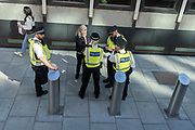 Met Police officers question a woman who shows them her phone during a stop and search procedure in Westminster, on 24th September 2021, in London, England.
