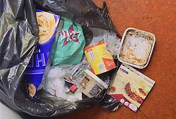 Overflowing dustbin bag full of kitchen waste,
