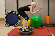 Partially-sighted skiing paralympian from the Sochi Olympics, Kelly Gallagher physio training at the Sports Centre in the University of Ulster, Belfast, Northern Ireland. Using a balance aide to simulate downhill skiing <br /> she finds the going hard as she starts a new training regime for the forthcoming winter season. Kelly Marie Gallagher, MBE is a Northern Irish skier and the first athlete from Northern Ireland to compete in the Winter Paralympics. Gallagher won Britain's first ever Winter Paralympic gold medal during Sochi 2014. From the chapter entitled 'The Law of Gravity' and from the book 'Risk Wise: Nine Everyday Adventures' by Polly Morland (Allianz, The School of Life, Profile Books, 2015).