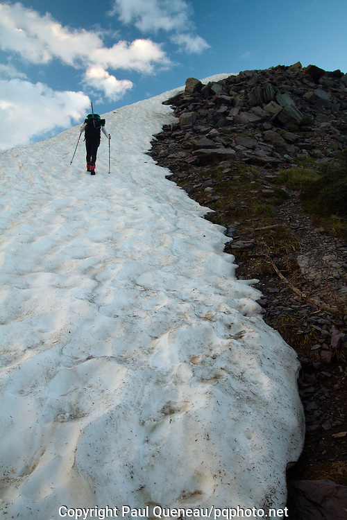 A backpacker climbs a snowfield to the summit of Lincoln Peak above Sperry Chalet in Glacier National Park, Montana.