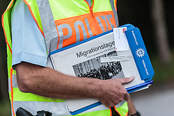 """25.09.2015, Grenzübergang, Freilassing, AUT, Fluechtlingskrise in der EU, im Bild Flüchtlinge an der Grenze zu Österreich, ein Poliziei Beamter mit einem """"Migrationslage"""" Dokument // Migrants on the Austrian Border, a Policemen with a """"migration situation"""" document. Thousands of refugees fleeing violence and persecution in their own countries continue to make their way toward the EU, border crossing, Freilassing, Germany on 2015/09/25. EXPA Pictures © 2015, PhotoCredit: EXPA/ JFK"""