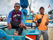 18 JULY 2016 - KUTA, BALI, INDONESIA:  Crewmen wait to board their small fishing canoe in the fish market at Pasar Ikan pantai Kedonganan.   PHOTO BY JACK KURTZ
