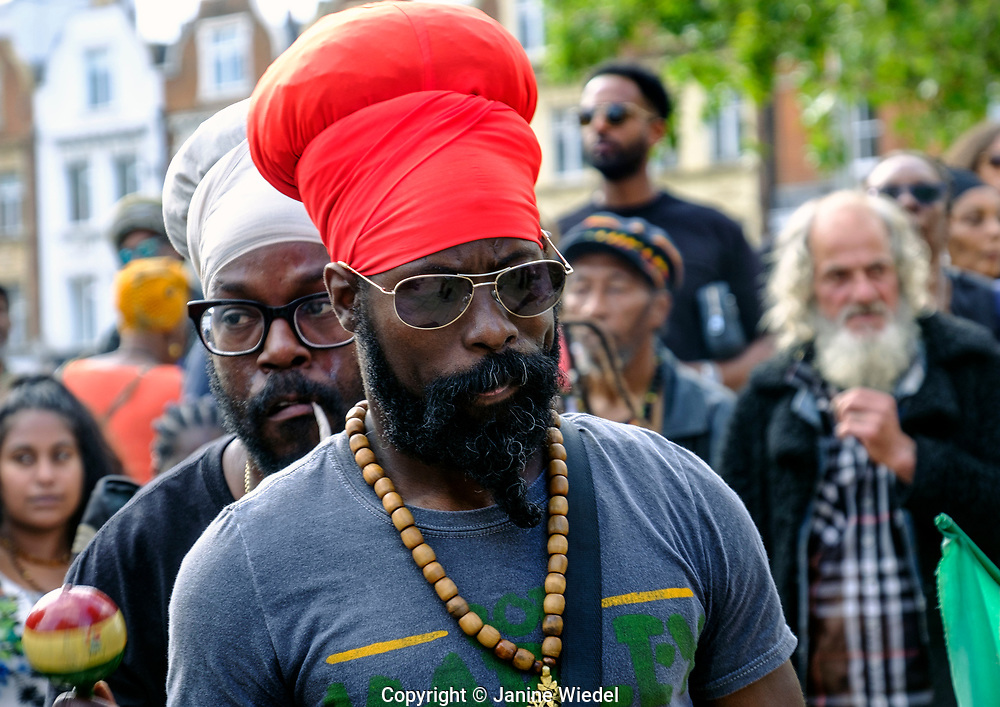 Listening to Groundation music at annual Reparations Rebellion event on Afrikan Emancipation Day in Windrush Square Brixton 2021.