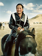 Trendy teenage girl in full leather outfit coming by horse from nearby Olgii town to see the festival.<br /> <br /> Eagle Hunting festival in Western Mongolia, in the province of Bayan Olgii. Mongolian and Kazak eagle hunters come to compete for 2 days at this yearly gathering. Mongolia