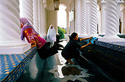 A light moment precedes a solemn occasion, as women prepare to pray  the second of the five pillars of Muslim faith  at the Omar Ali Saifuddien Mosque in Brunei's capital of Bandar Seri Begawan.  Mother and daughters was before enter the pray hall, following the Quran's command that worshippers should be clear of body as well as soul. © Steve Raymer 2002 / ALL RIGHTS RESERVED