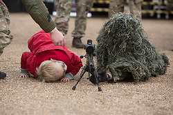 © Licensed to London News Pictures. 26/10/2013. Horseguards, London. Reese (6) peers at a soldier in camouflage at an Armed Reserves recruiting event in central London today.  The Army Reserve who are aiming to boost their numbers to 30,000 by the end of 2018.   Photo credit: Alison Baskerville/LNP