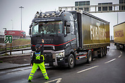 Police manage freight lorry drivers as the French border closures due to a new strain of COVID-19 at the entrance into the port of Dover in the Eastern Dock where the cross channel port is situated with ferries departing to go to Calais in France on the 21st of December 2020, Dover, Kent, United Kingdom. Dover is the nearest port to France with just 34 kilometres 21 miles between them. It is one of the busiest ports in the world. As well as freight container ships it is also the main port for P&O and DFDS Seaways ferries.