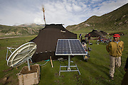 Tibetan nomads outside their handmade yak-wool tents where they make their home in spring and summer on the Tibetan Plateau.  The satellite dish was provided by China's central government; along with a solar battery charger, a truck battery, and a TV so the nomads can watch Chinese broadcasts and learn the Chinese language; an attempt, some say, to assimilate indigenous Tibetans.