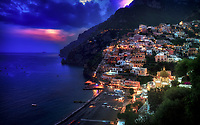 """""""The magical twilight time of Positano""""...<br /> <br /> After an exhilarating drive along the high cliffs on the Amalfi coast from Sorrento down to Positano, I found myself in sensory overload with its beauty and photogenic appeal. After circling around the entire village and its cliffside three times on Positano's only street, which was a single lane winding down from the top and back up and over to where I began, I finally found the parking garage by the hotel, about 2/3rds up the facing village in this image. The climb down the winding road and steep staircases made for quite a workout in the hot late May sun. Reaching the beach and marina, I forgot about my exhaustion and could not capture enough of Positano's plush beauty; however, the large amount of tourists and bright sun did not allow for ideal conditions. Walking the length of the beach, I found a very, very steep staircase leading straight up to a large veranda at the Albergo California. Taking an exhaustive seat on a plush lounge chair with a perfect view to watch the sunset behind the Amalfi Cliffs, I was taken back by a pleasant Italian (Positano) waiter from the hotel offering a towel, ice water, and drinks for the evening. I expressed that I was not staying at the hotel, but he didn't seem to mind and proceeded to educate me on the culture of this historic resort village. The sunset was being coy and didn't appear to cooperate, but during opportune moments it mystified the ominous clouds, and contributed just enough light and color to satisfy a weary photographer."""