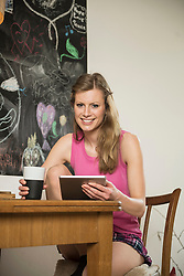 Young woman using digital tablet and having coffee, Munich, Bavaria, Germany