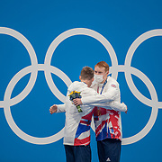 TOKYO, JAPAN - JULY 27: Tom Dean of Great Britain is  with his gold medal on the podium is is congratulated by silver medal winner and team mate Duncan Scott of Great Britain after winning the 200m freestyle for men during the Swimming Finals nat the Tokyo Aquatic Centre at the Tokyo 2020 Summer Olympic Games on July 27, 2021 in Tokyo, Japan. (Photo by Tim Clayton/Corbis via Getty Images)